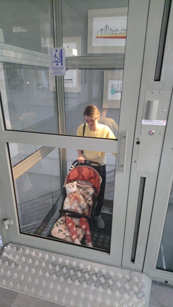 matka  i dziecko z wózkiem w windzie