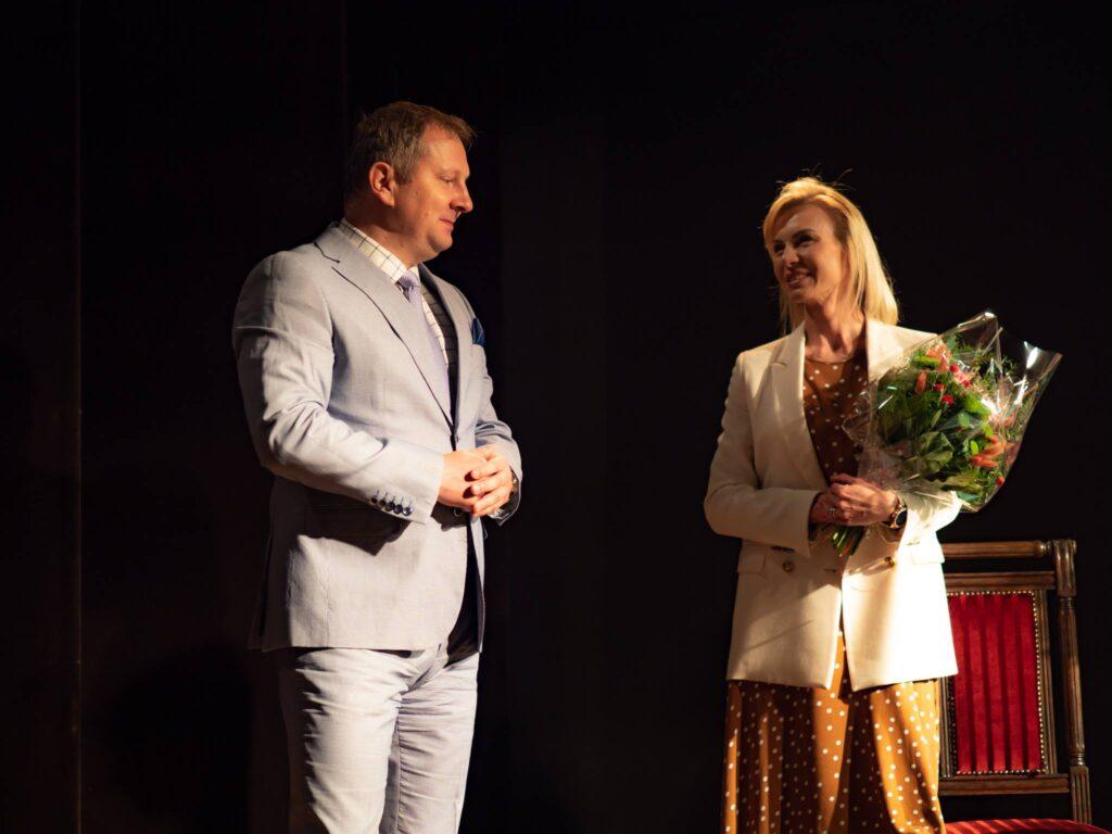 Stojący mężczyzna oraz kobieta trzymająca kwiaty
