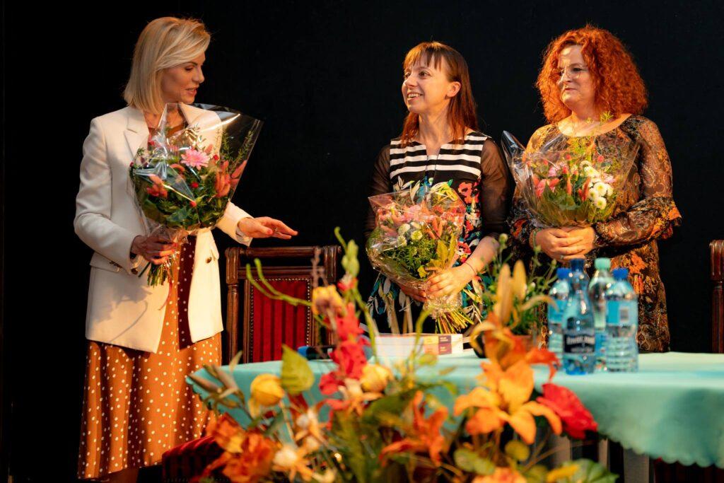Trzy kobiety trzymające kwiaty