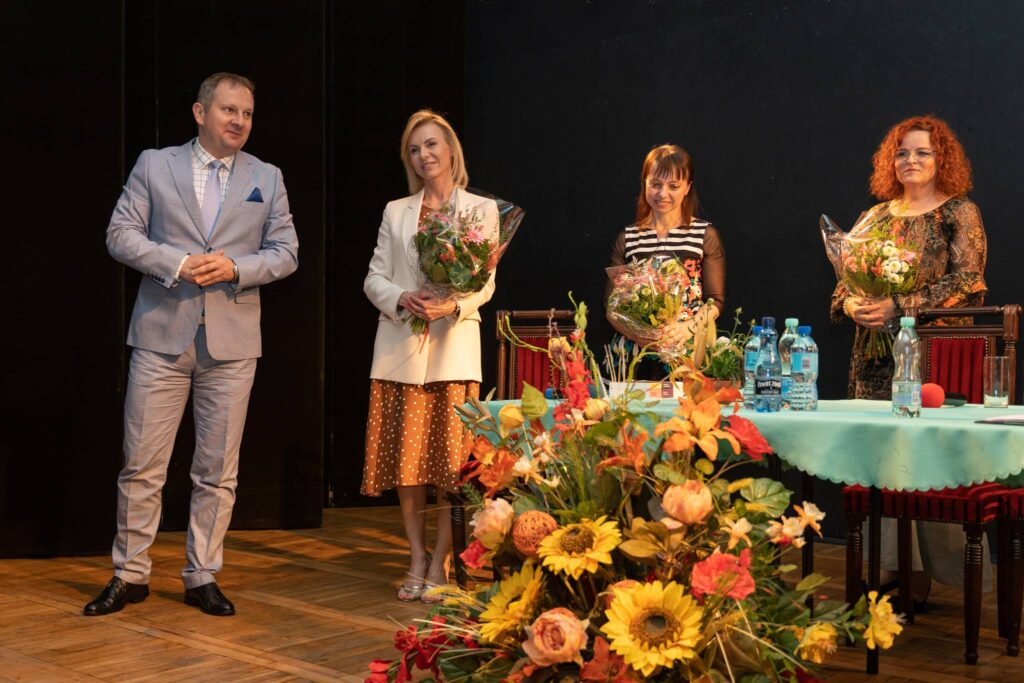 Stojący mężczyzna oraz trzy kobiety z trzymające kwiaty