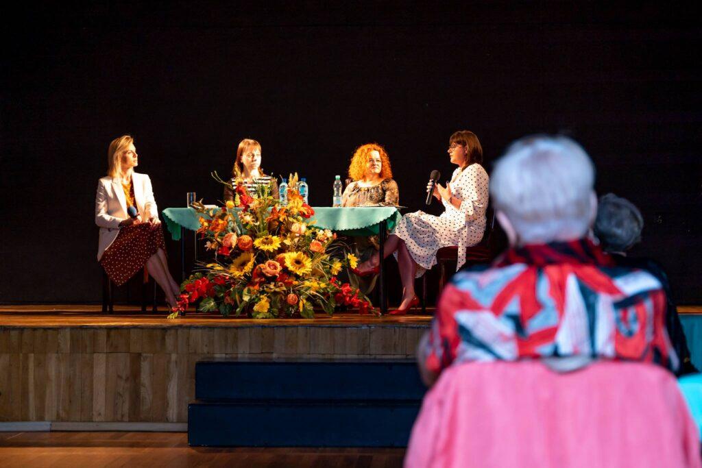Cztery kobiety siedzące przy stole, jedna z nich trzyma mikrofon